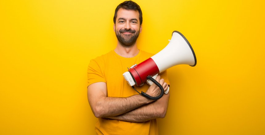 Man on isolated vibrant yellow color holding a megaphone